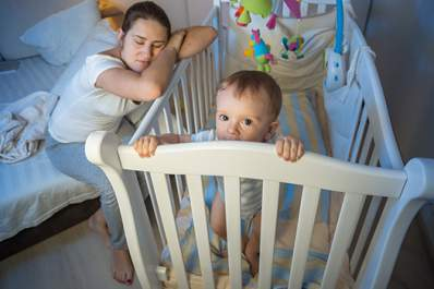 Tired mother asleep next to awake baby's crib