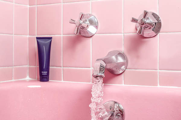 Water running from faucet of pink tiled bath
