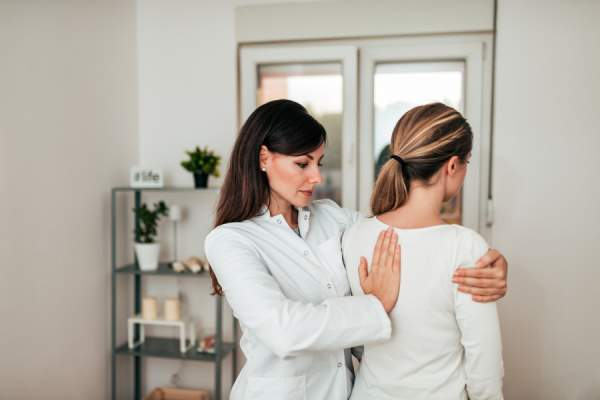 Physiotherapist examining and correcting patient's posture
