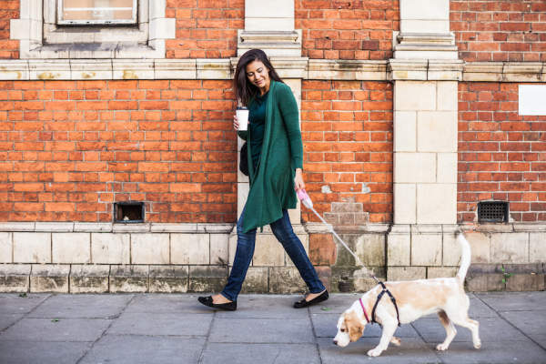 Young woman walking dog in morning.