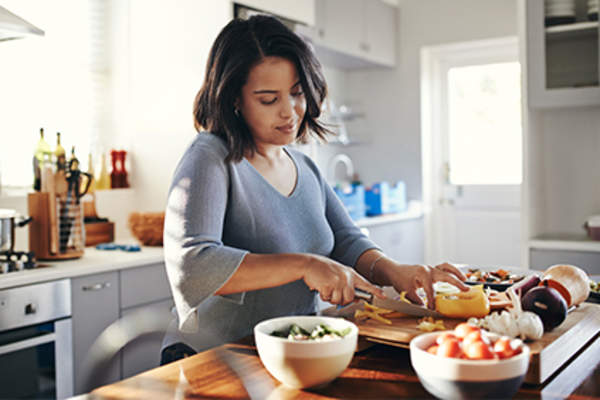 Young woman chopping in the kitchen to make a healthy meal.