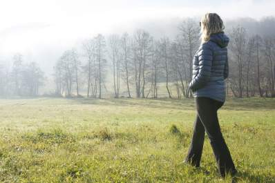 Woman taking a morning walk in a field.