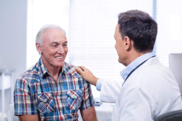 Older man consulting with doctor.