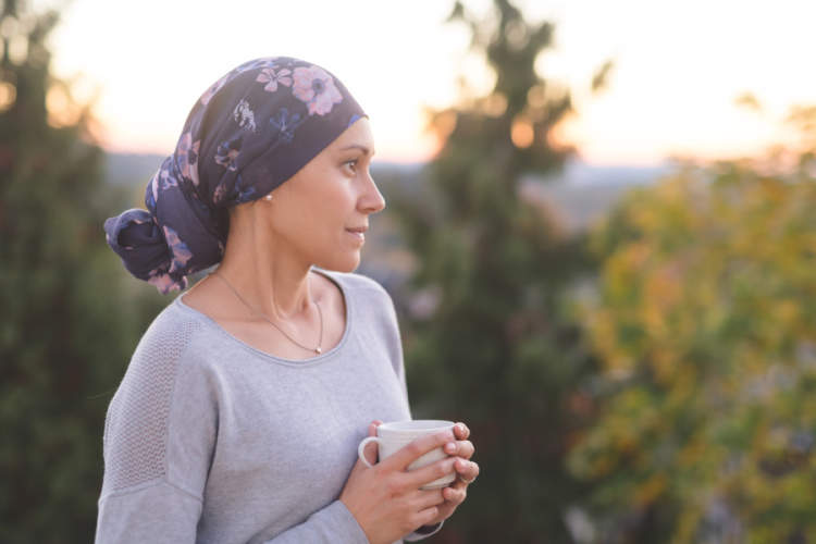 woman with cancer wearing headscarf, drinking tea, standing outside