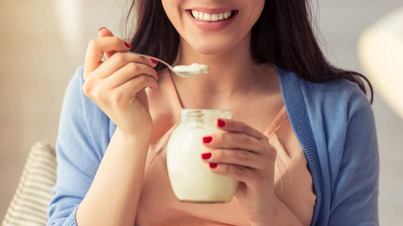 Smiling woman eating yogurt.