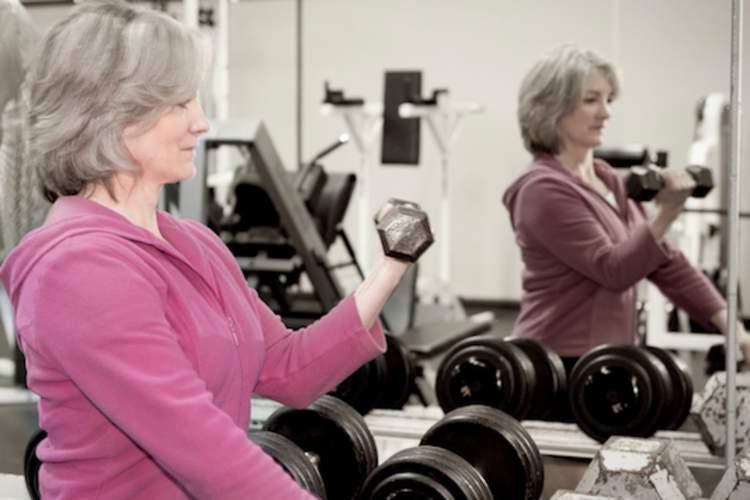 在健身房对着镜子锻炼的女人。