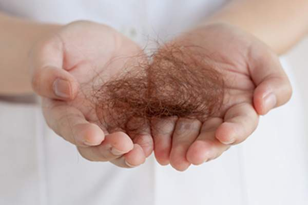 Pile of hair in woman's hand
