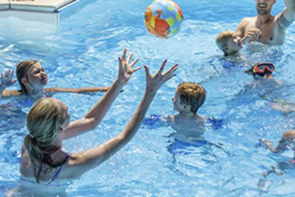 family playing in swimming pool image