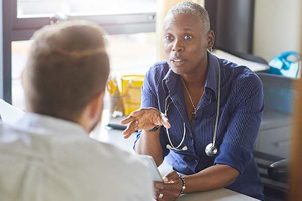 Female doctor discussing treatment with male patient.