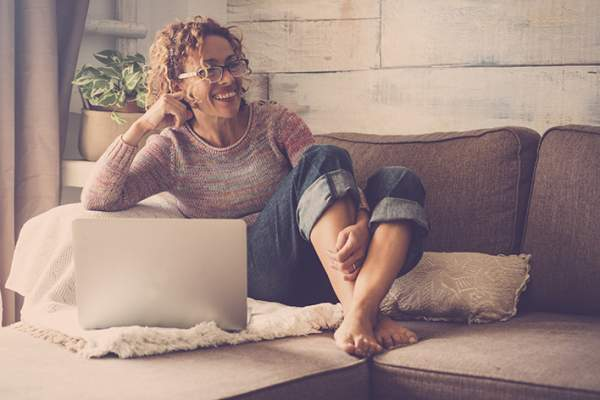 Woman with chronic pain relaxing on her couch with a laptop.