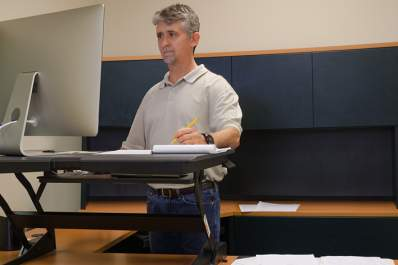 Man working at an adjustable sit-stand desk work station.