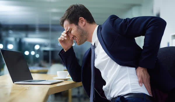 Man in pain at office desk.