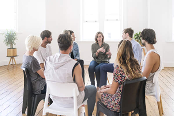 Young woman talking at support group meeting.
