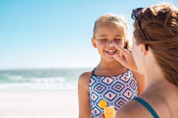 mom putting sunscreen on daughter's face