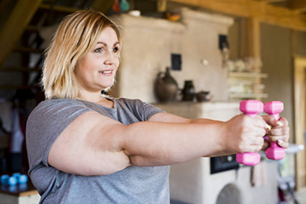 Woman exercising with arm weights.