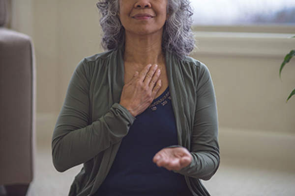Senior woman practicing deep breathing techniques.