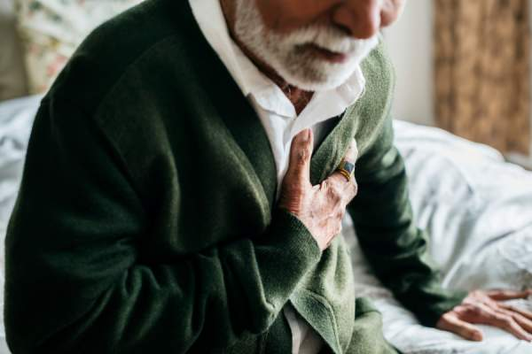 Elderly man clutching heart