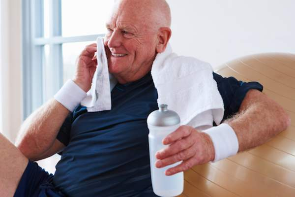Smiling senior man drinking water after exercise.