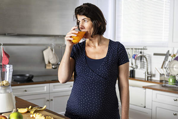 Woman drinking a glass of orange juice.