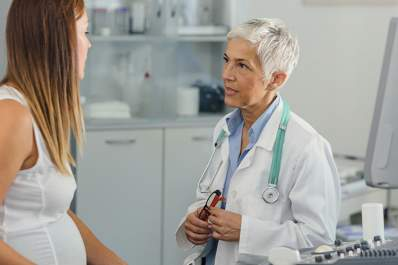 Doctor talking to young pregnant woman about flu risks.