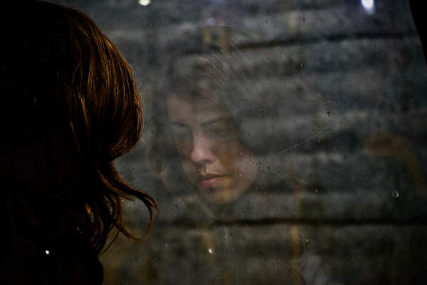 Sad woman from behind looking into window with face reflection