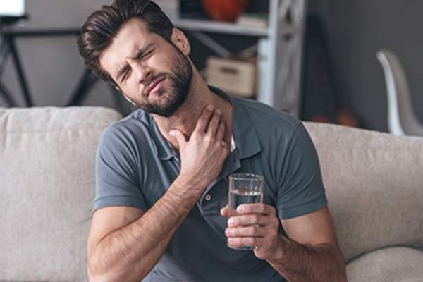 Man having trouble swallowing while drinking a glass of water.