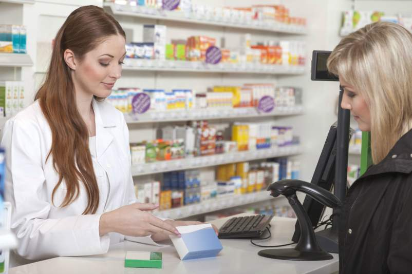 Pharmacists talking with woman
