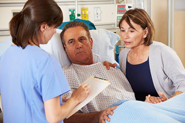 Woman explaining to nurse about what happened to her husband.