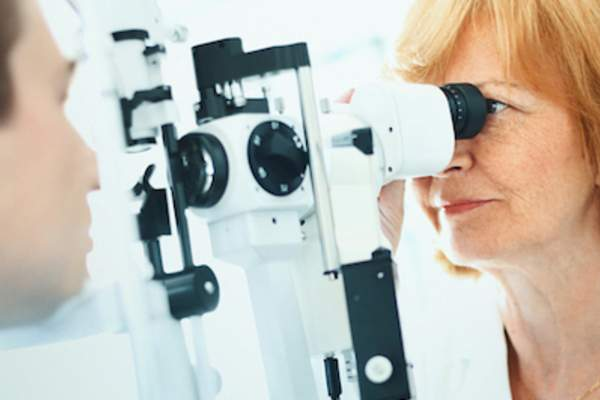 Man having eyes examined by opthamologist.