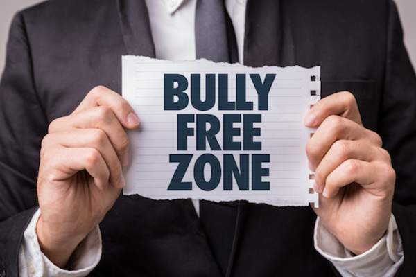 Principle holding bully free zone sign.