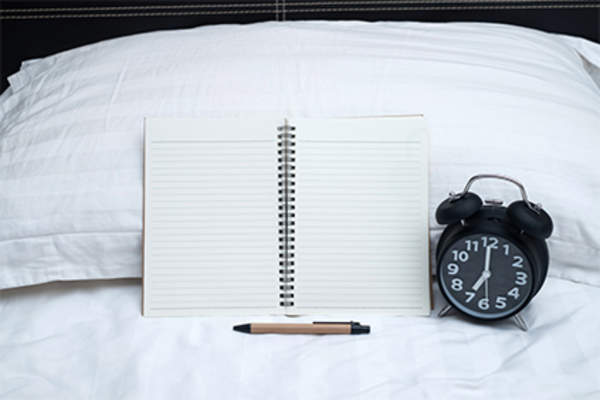 Sleep journal, pen, alarm clock on bed.
