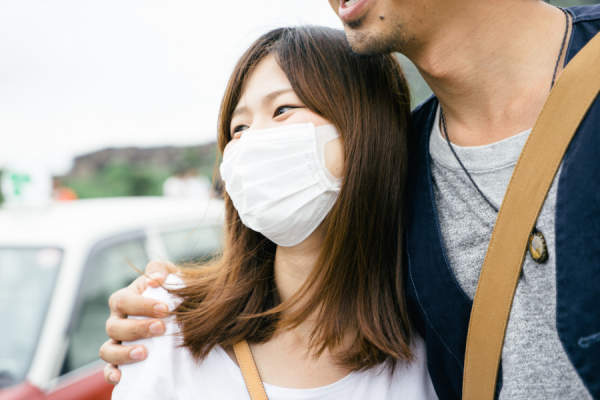 woman wearing surgical mask outdoors with man not wearing surgical mask