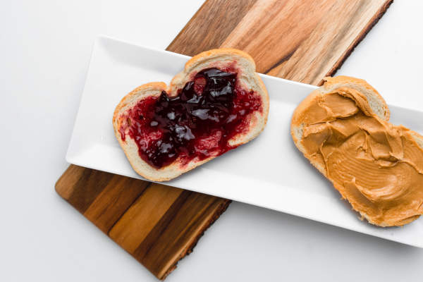 peanut butter and jelly sandwich on white bread split in two