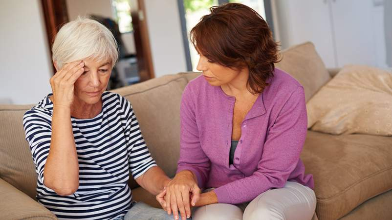 Woman comforting a senior with acute stressed disorder.