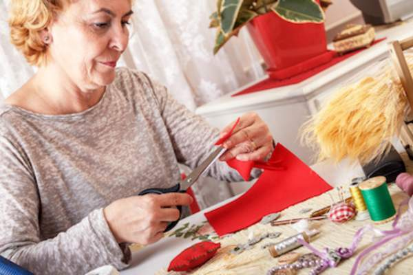 Woman using scissors to cut felt.
