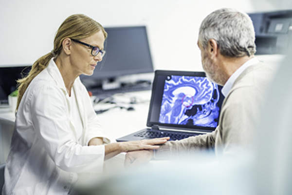 Doctor watching her patient's brain tumor progress.