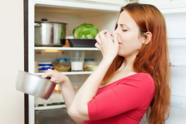 Woman pulling something stinky from refrigerator.