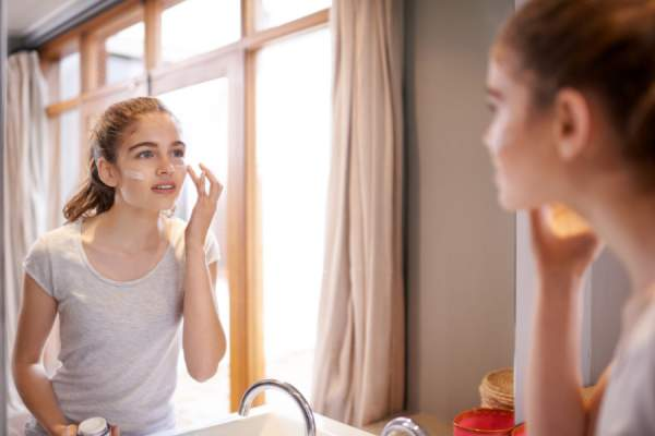 young woman putting on face cream