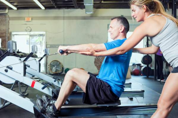 Personal trainer training older male client.