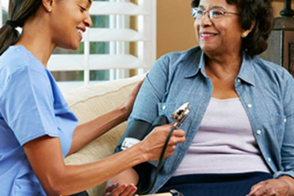 nurse checking woman with diabetes blood pressure image