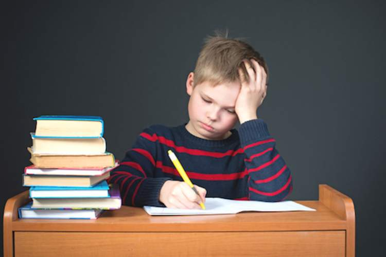 Child with migraine struggling with school work.