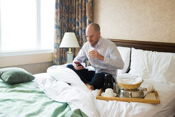 Man relaxing in hotel room with room service.