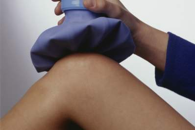 A woman holds an ice pack on her knee.