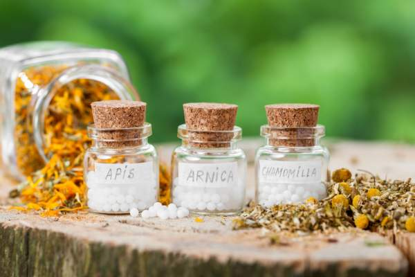 Three bottles of homeopathy globules and healthy herbs
