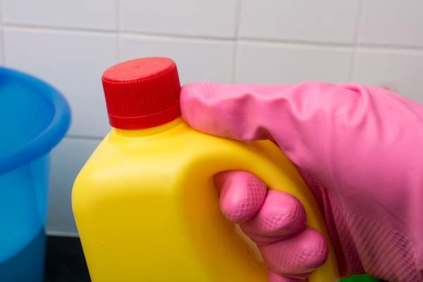 Someone wearing a glove holding a bottle of ammonia.