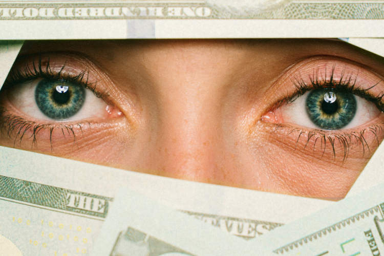 money completely obscuring a woman's face except her eyes