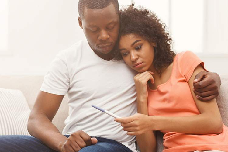 Disappointed couple holding negative pregnancy test.