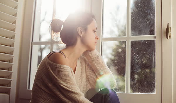 Unhappy woman sitting near the window.