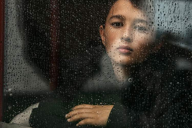 Sad young boy through rainy window.