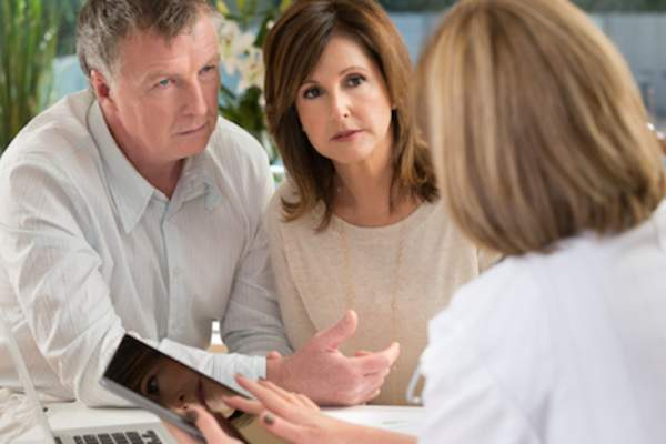 Doctor speaking with worried patient and spouse